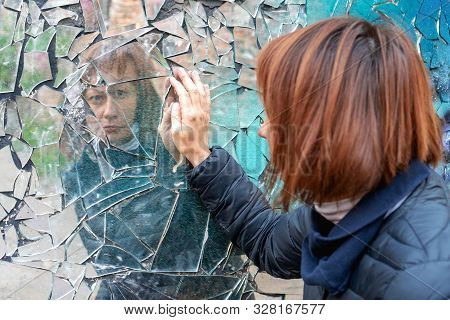 Woman Looks In A Broken Mirror And Shows Her Hand On A Mirror. The Concept Of Human Emotions