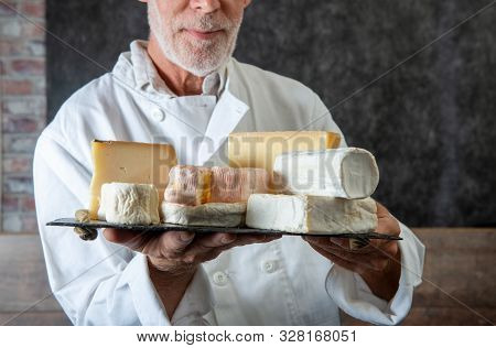 Man Holding A Tray With The  Various French Cheeses