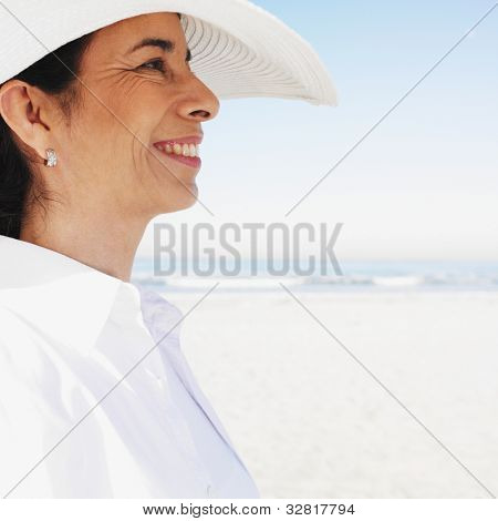Hispanic woman wearing sunhat at beach
