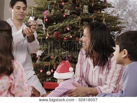 Hispanic father video recording family on Christmas