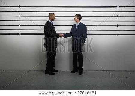 Multi-ethnic businessmen shaking hands in police line up