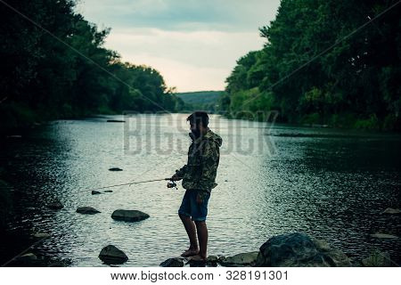 Fishing Became A Popular Recreational Activity. Handsome Fisherman Fishing In A River With A Fishing