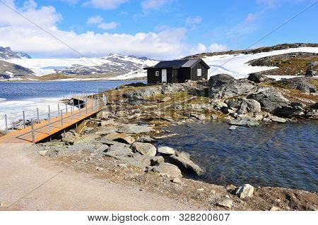 Black Wooden House With Snowy Landscape