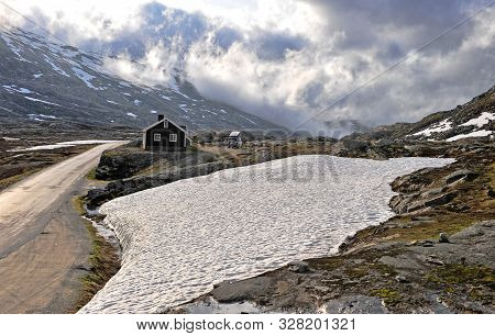 Lonely Black House In Mountains On Snowy Road