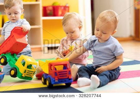 Little Toddlers Boys And A Girl Playing Together In Nursery Or Creche. Preschool Children In Day Car