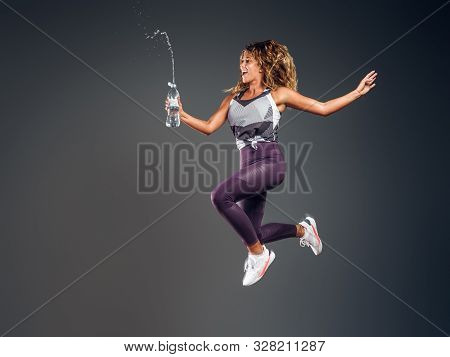 Joyful Energising Woman Is Jumping At Photo Studio With Bolle Of Water Making, Splashes.