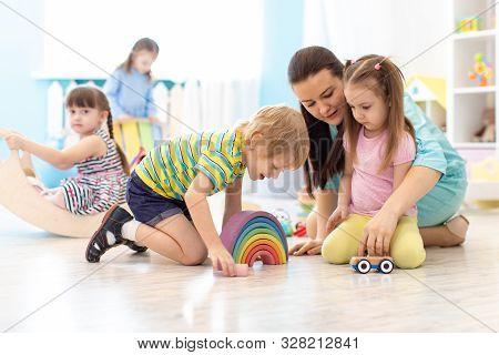 Children Group Playing In Kindergarten. Kids With Teacher In Class