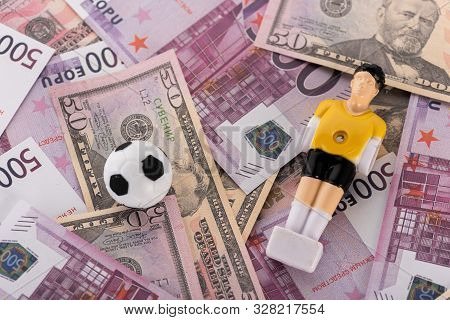 Toy Soccer Ball And Football Player On Euro And Dollar Banknotes, Sports Betting Concept