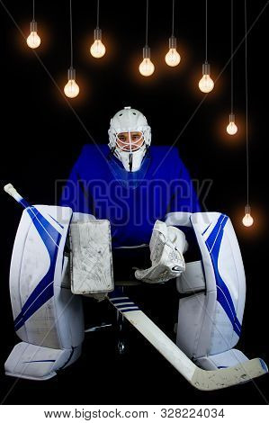 Hockey Goalie In Complete Hockey Outfit Sitting On Office Chair. Above Him Are Lamps With A Light Bu