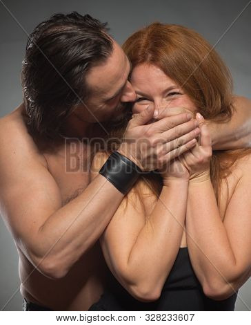 Hilarious joke. Cheerful shirtless man standing behind his bare shouldered positive wife while covering her mouth with hands and feeling pleased poster