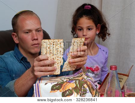 Jewish Family Celebrating Passover.jewish Man Blessing On Matzah As They Celebrate Seder. The Feast