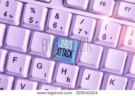 Writing note showing Ddos Attack. Business photo showcasing perpetrator seeks to make network resource unavailable White pc keyboard with note paper above the white background. poster