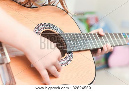 Girl Learns To Play Guitar During A Music Lesson On The Instrument