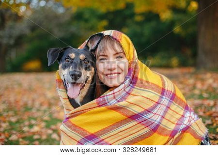 Woman Wrapped In Woollen Blanket With Dog In Autumn Fall Park. Beautiful Happy Young Caucasian Woman