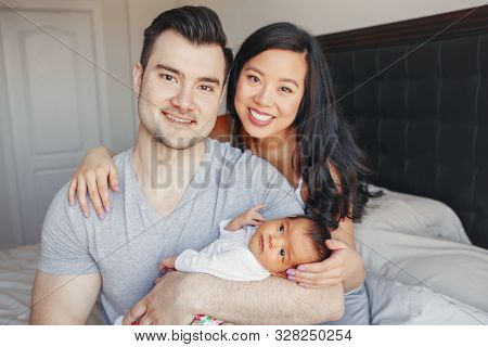 Beautiful Smiling Chinese Asian Mother And Caucasian Father With Newborn Infant Baby Child. Happy Fa
