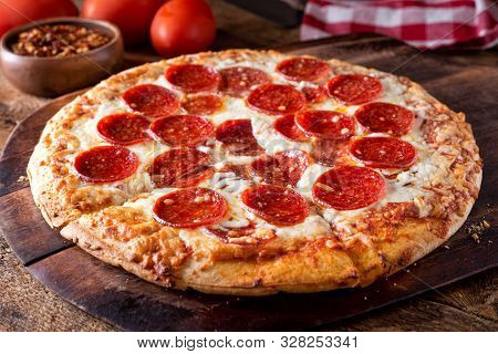 A Delicious Brick Oven Baked Pepperoni Pizza On A Rustic Wood Serving Board.
