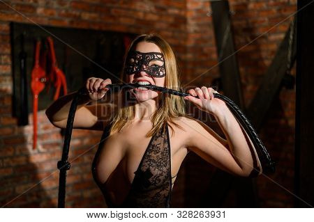 Bdsm A Masked Woman Bites A Leather Whip. Games For Adults. Stikini Crosses. Sexy Blonde In Lace Bla