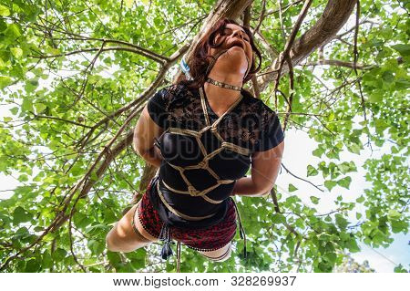 A Young Girl Suffering In Pain And Hanging Her Core And Chest From A Tree - Her Body Tied With Ropes