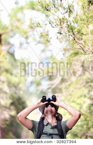 Binoculars - man hiker looking up at copy space during outdoors hiking trip.