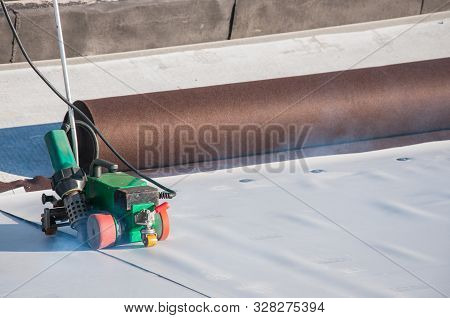 Construction Device For Installing Waterproofing Materials On The Roof. Installation Of Waterproofin