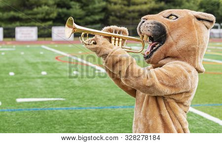A Cougar Mascot Standing Sideways Pretending To Play A Trumpet With The Athletic Field In The Backgr