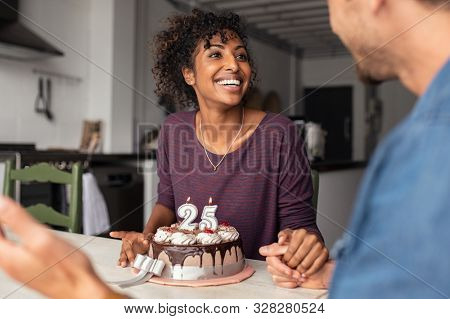 Multiethnic couple sitting at table and celebrating birthday at home. Young african girl surprised on seeing 25th birthday cake with her boyfriend. Excited wife celebrating birthday with husband.