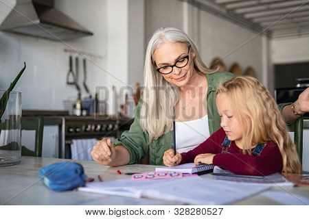 Mature grandmother helping child with homework at home. Satisfied old grandma helping her granddaughter studying in living room. Little girl writing on notebook with senior teacher sitting next to her
