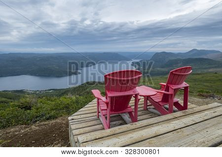 Two Red Adirondack Chairs On Top Of The Lookout Trail In Gros Morne National Park Newfoundland