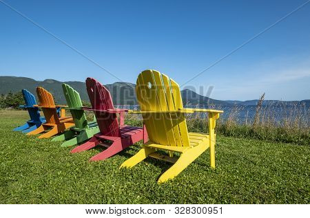 A Row Of Bright And Colorful Adirondack Chairs Facing Bonne Bay On A Sunny Day In Newfoundland