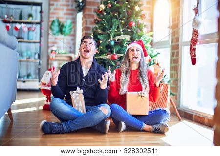 Young couple wearing santa claus hat sitting on the floor around christmas tree at home crazy and mad shouting and yelling with aggressive expression and arms raised. Frustration concept.