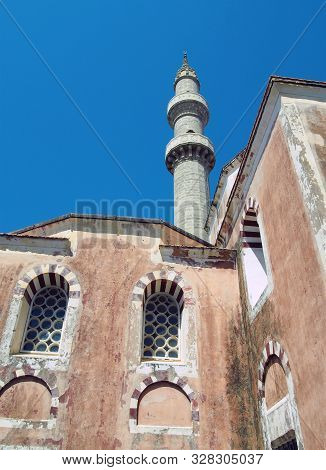 The Suleiman Mosque In Rhodes Old Town With Tall Minaret Against A Blue Sunlit Sky