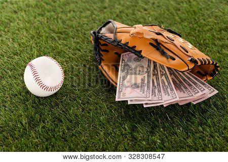 Dollar Banknotes In Baseball Glove Near Ball On Green Grass, Sports Betting Concept
