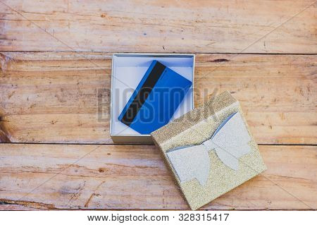 Payment Card Or Gift Card Inside Open Present Box On Wooden Table, Concept Of Shopping And Celebrati