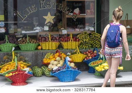 Sao Miguel Island, Azores - June 28, 2019: A Young Girl Standing Outside Of A Grocery Store Looking
