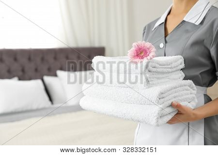 Chambermaid With Stack Of Fresh Towels In Hotel Room, Closeup. Space For Text