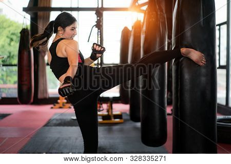 Portrait Of Asian Confident Young Boxer Woman With Blue Boxing Gloves, Kicking A Bag Boxing In Profe