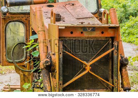 Radiator And Front Of Rusted, Broken Down Bulldozer Sitting On Abandoned Unused Road In Wilderness.