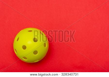 Bright Yellow Pickleball Or Whiffle Ball On A Solid Bright Red Flat Lay Background Symbolizing Sport