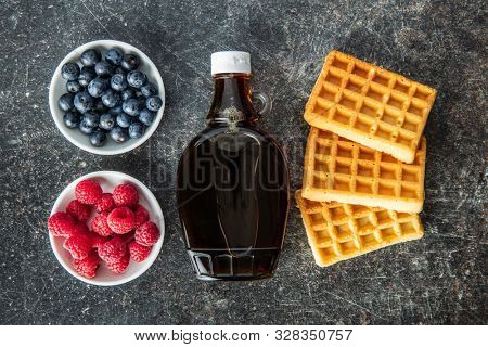 Waffles, maple sirup, blueberries and raspberries on old kitche table. Top view. Flat view.