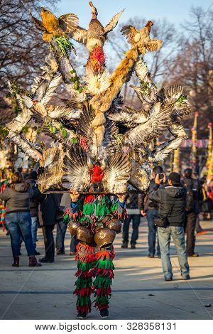 Mummers perform rituals to scare evil spirits at Surva festival at Pernik in Bulgaria. The people with the masks are called Kuker (kukeri). Wood mask with feathers and chickens.
