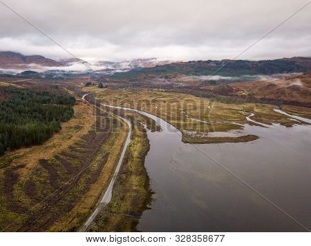 Road Passing Around Loch Eil And Overlooking The Brown Wintery Scottish Highlands On An Overcast Gre