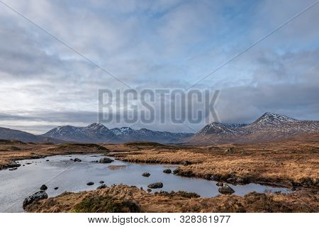 Brown Wintery Grass Fields Overlooking Black Mount Mountain Range On A Partially Cloudy Day In The S