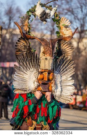 Mummers perform rituals to scare evil spirits at Surva festival at Pernik in Bulgaria. The people with the masks are called Kuker (kukeri). Wood mask with feathers and pigeon.
