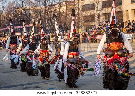 Mummers perform rituals to scare evil spirits at Surva festival at Pernik in Bulgaria. The people with the masks are called Kuker (kukeri). Dancers with big bells.