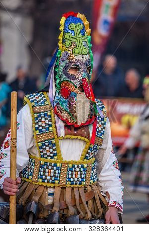Mummers perform rituals to scare evil spirits at Surva festival at Pernik in Bulgaria. The people with the masks are called Kuker (kukeri). Colorful mask.