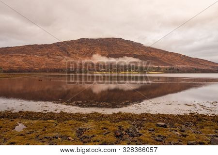 Calm Waters At Loch Eil With A View Of The Wintery And Brown Scottish Highlands On Cloudy Day.