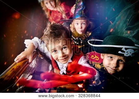 Happy children in carnival costumes trick or treating on Halloween.