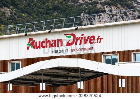 Guilherand-granges, France - October 17, 2019. Logo And Building Of French Retailer Auchan And The D