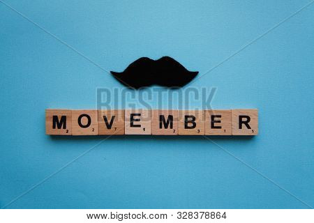 Scrubble Letters Movember Concept On The Blue Background With Black Moustache. Preventing Prostate C