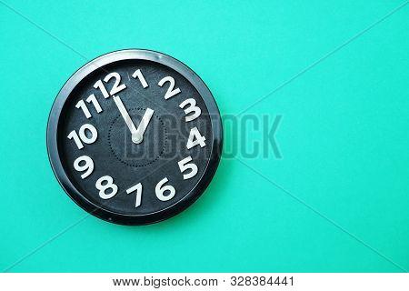 Black Round Clock Showing Ten O'clock On Green Background